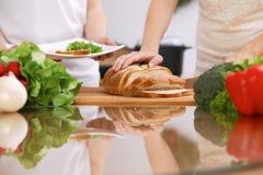 Plan rapproché des mains humaines faisant cuire dans la cuisine Mère et fille ou deux amis féminins coupant le pain Repas sain Photo stock