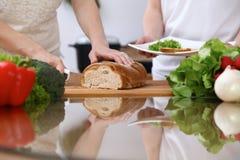 Plan rapproché des mains humaines faisant cuire dans la cuisine Pain de coupe de mère et de fille ou de deux femelles à la table  Photo libre de droits