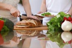 Plan rapproché des mains humaines faisant cuire dans la cuisine Pain de coupe de mère et de fille ou de deux femelles à la table  Photo stock