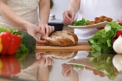 Plan rapproché des mains humaines faisant cuire dans la cuisine Pain de coupe de mère et de fille ou de deux femelles à la table  Photos stock