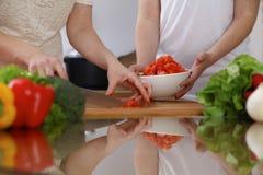 Plan rapproché des mains humaines faisant cuire dans la cuisine Tomate de coupe de mère et de fille ou de deux femelles pour la s Image libre de droits