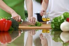 Plan rapproché des mains humaines faisant cuire dans une cuisine Amis ayant l'amusement tout en préparant la salade fraîche Végét Photo stock