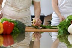 Plan rapproché des mains humaines faisant cuire dans une cuisine Amis ayant l'amusement tout en préparant la salade fraîche Végét Photographie stock libre de droits