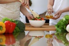 Plan rapproché des mains humaines faisant cuire dans une cuisine Amis ayant l'amusement tout en préparant la salade fraîche Végét Image stock
