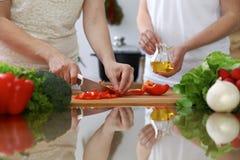 Plan rapproché des mains humaines faisant cuire dans une cuisine Amis ayant l'amusement tout en préparant la salade fraîche Végét Photos libres de droits
