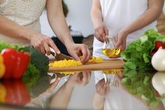 Plan rapproché des mains humaines faisant cuire dans une cuisine Amis ayant l'amusement tout en préparant la salade fraîche Végét Images libres de droits