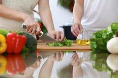 Plan rapproché des mains humaines faisant cuire dans une cuisine Amis ayant l'amusement tout en préparant la salade fraîche Végét Photographie stock
