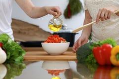 Plan rapproché des mains humaines faisant cuire dans une cuisine Amis ayant l'amusement tout en préparant la salade fraîche Végét Images stock
