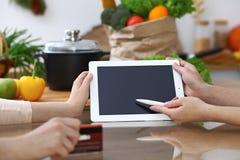 Plan rapproché des mains humaines se dirigeant dans le comprimé dans la cuisine Amis ayant l'amusement tout en choisissant le men Photos libres de droits