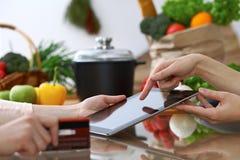 Plan rapproché des mains humaines se dirigeant dans le comprimé dans la cuisine Amis ayant l'amusement tout en choisissant le men Images libres de droits