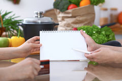 Plan rapproché des mains humaines se dirigeant dans le secteur d'espace de copie de carnet dans la cuisine Amis ayant l'amusement Image stock