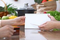 Plan rapproché des mains humaines se dirigeant dans le secteur d'espace de copie de carnet dans la cuisine Amis ayant l'amusement Photos libres de droits