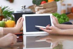 Plan rapproché des mains humaines se dirigeant dans le secteur d'espace de copie de carnet dans la cuisine Amis ayant l'amusement Photos stock