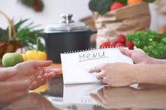 Plan rapproché des mains humaines se dirigeant dans le secteur d'espace de copie de carnet dans la cuisine Amis ayant l'amusement Images stock