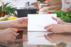 Plan rapproché des mains humaines se dirigeant dans le secteur d'espace de copie de carnet dans la cuisine Amis ayant l'amusement Photo libre de droits
