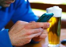 Plan rapproché des mains masculines avec le fond futé de téléphone et de bière Photo stock