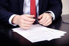 Plan rapproché des mains masculines avec le stylo au-dessus du document image stock