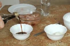 Plan rapproché des mains masculines faisant la sauce à poulet Versez la sauce de soja dans un plat images libres de droits