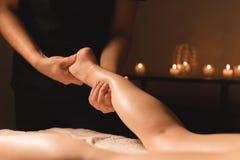 Plan rapproché des mains masculines faisant le massage de veau des jambes femelles dans une chambre noire avec des bougies à l'ar photographie stock