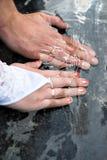 Plan rapproché des mains des nouveaux mariés avec des anneaux de mariage Image stock
