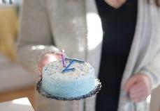 Plan rapproché des mains portant le gâteau d'anniversaire avec la bougie pour le ` s f de bébé photo libre de droits
