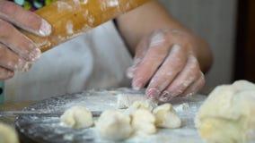 Plan rapproché des mains supérieures de femme roulant des morceaux de pâte avec la goupille clips vidéos