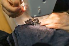 Plan rapproché des mains une femme de Yong sur la machine à coudre, t piquant Image libre de droits