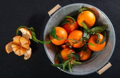 Plan rapproché des mandarines avec des feuilles dans une cuvette en métal image stock