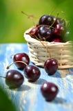 Plan rapproché des merises mûres, fraîches et dans le panier en osier sur la table Images stock