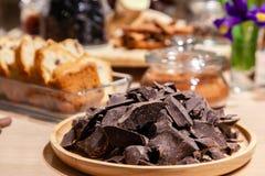 Plan rapproché des morceaux de chocolat foncé naturel d'un plat en bois rond sur le fond des bonbons, pâtisseries pour la dégusta photo libre de droits