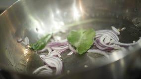 Plan rapproché des oignons de torréfaction dans la casserole action La cuisson commence par des oignons de torréfaction assaisonn photo stock