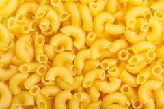Plan rapproché des pâtes italiennes crues - macaronis de coude Image stock