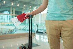 Plan rapproché des passeports avec la carte d'embarquement et les bagages dans des mains masculines à l'aéroport Homme de tourist Images stock