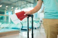 Plan rapproché des passeports et de la carte d'embarquement dans des mains masculines à l'aéroport Images stock