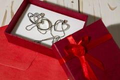 Plan rapproché des pendants argentés de coeur dans un boîte-cadeau rouge et une ENV rouge Photographie stock