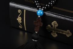 Plan rapproché des perles de Sainte Bible et de chapelet avec la croix sur le fond noir Concept et foi de religion images libres de droits