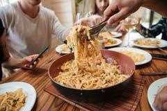 Plan rapproché des personnes mangeant des pâtes sur la cuisine à la maison Photo libre de droits