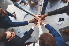 Plan rapproché des personnes tenant des mains ensemble tout en se reposant autour du bureau Images libres de droits