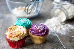 Plan rapproché des petits gâteaux devant des ustensiles de cuisine Photos stock