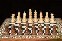 Plan rapproché des pièces d'échecs sur un échiquier en bois Images libres de droits