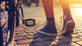 Plan rapproché des pieds d'homme de hippie et des roues de bicyclette de ville, vue arrière et activité de week-end de vacances d Photos stock