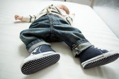 Plan rapproché des pieds de bébé garçon dans les jeans et des espadrilles se trouvant sur le lit Photo stock