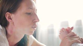 Plan rapproché des pieds de baiser de jeune jolie maman de son bébé et sourire Pieds de chéri dans des mains de mère clips vidéos