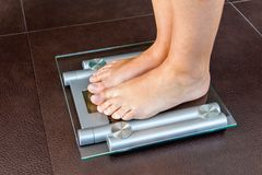 Plan rapproché des pieds de femme se tenant sur l'échelle de salle de bains Images stock