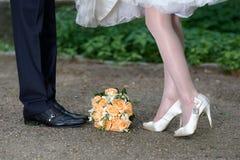 Plan rapproché des pieds de jeunes mariés et bouquet de mariage des fleurs photo stock