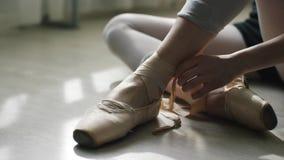 Plan rapproché des pieds de la ballerine sur un plancher en bois léger Fille attachant le ruban des chaussures de pointe banque de vidéos