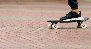 Plan rapproché des pieds de planchistes dans des espadrilles sur la planche à roulettes sur la route Photo stock