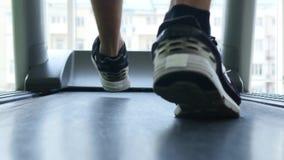 Plan rapproché des pieds du ` s d'athlète fonctionnant sur le tapis roulant banque de vidéos
