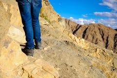 Plan rapproché des pieds du ` s de voyageur marchant vers le haut sur la dune de montagne et de sable au-dessus du ciel bleu Photographie stock libre de droits