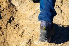 Plan rapproché des pieds du ` s de voyageur marchant vers le haut sur la dune de montagne et de sable - concept de voyage, de vac Images libres de droits